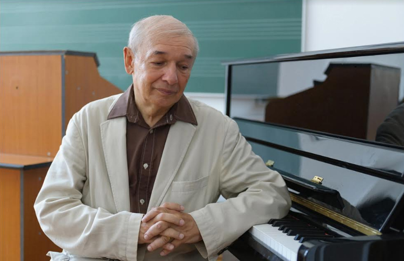 Octavian Nemescu sitting next to a piano.