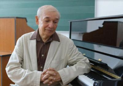 Octavian Nemescu sitting next to a piano.